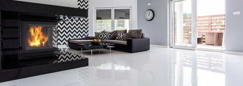 salotto moderno con camino design, pavimento bianco lucido e divano ad angolo.