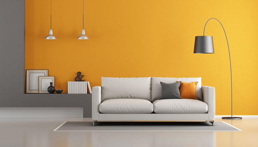 salotto con parete colorate arancione e grigio, divano grigio chiaro e pavimento grigio.