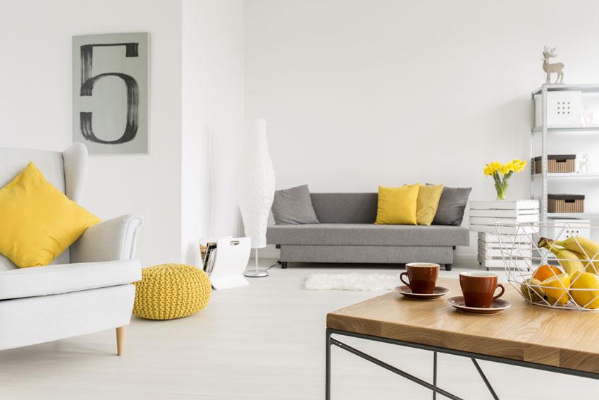 soggiorno bianco con cuscini gialli, tavolino in legno con frutta.