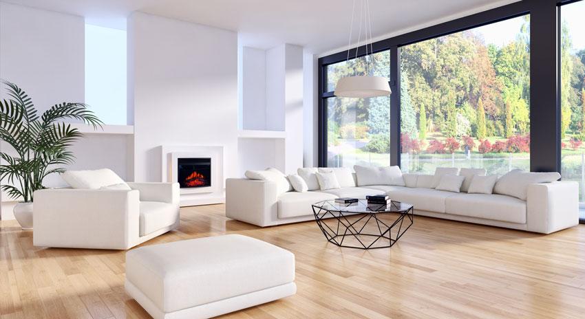 grande salotto con divano angolare bianco, bellissimo parquet marrone chiaro e camino elettrico.
