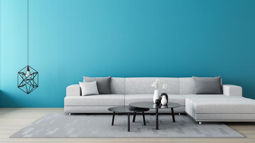 soggiorno con divano ad angolo grigio e parete color azzurro, lampadario design a sospensione.