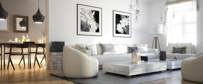 arredamento minimal, divano bianco con quadri bianchi e nero, grande tappeto grigio.