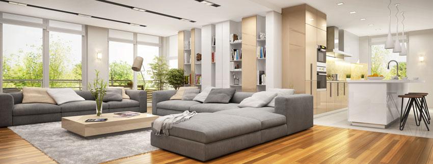 grande salotto con divano angolare, parquet, e cucina a vista.
