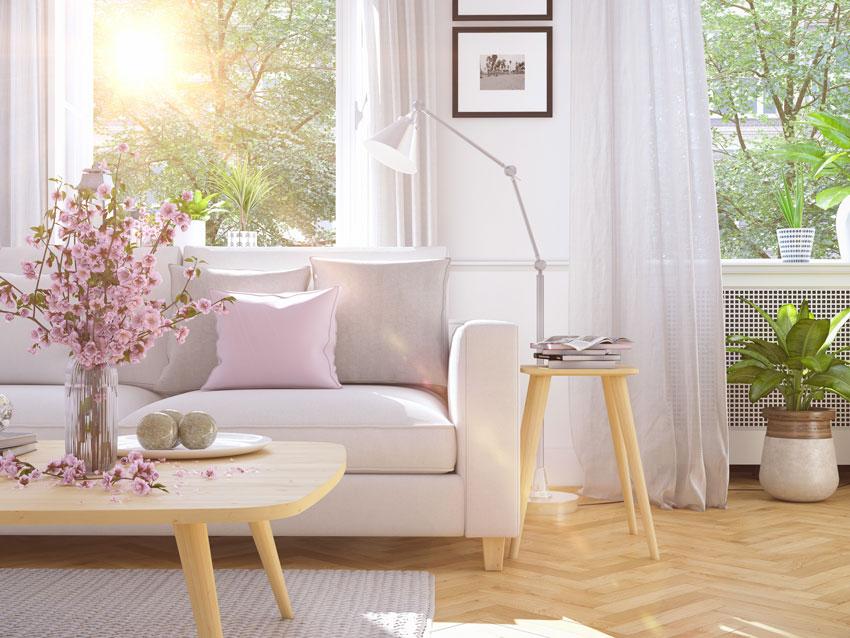 divano bianco con cuscino rosa, tavolino in legno con vaso di fiori primaverile.