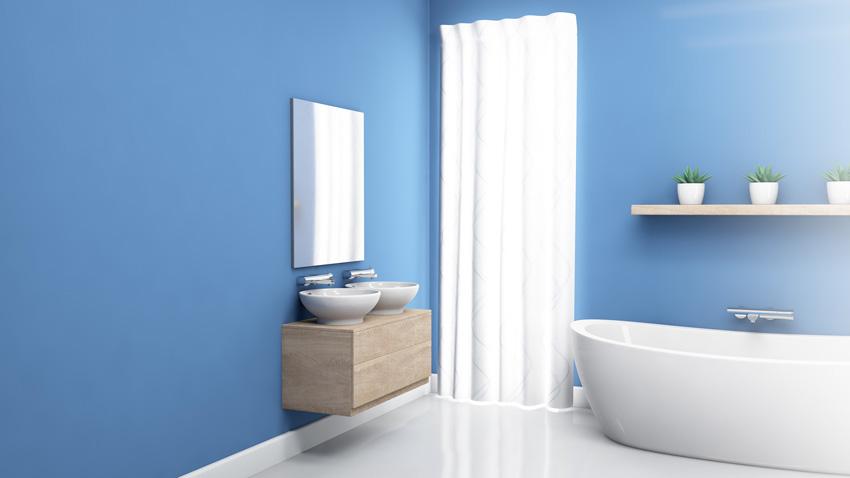 tenda bianca per il bagno che si abbina perfettamente con la vasca, risalta con le pareti blu.