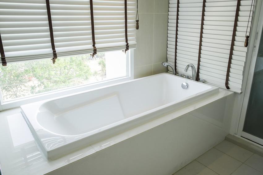vasca da bagno nascosto con tende veneziane.