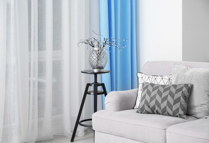 Tende coprenti azzurre con divano grigio chiaro.