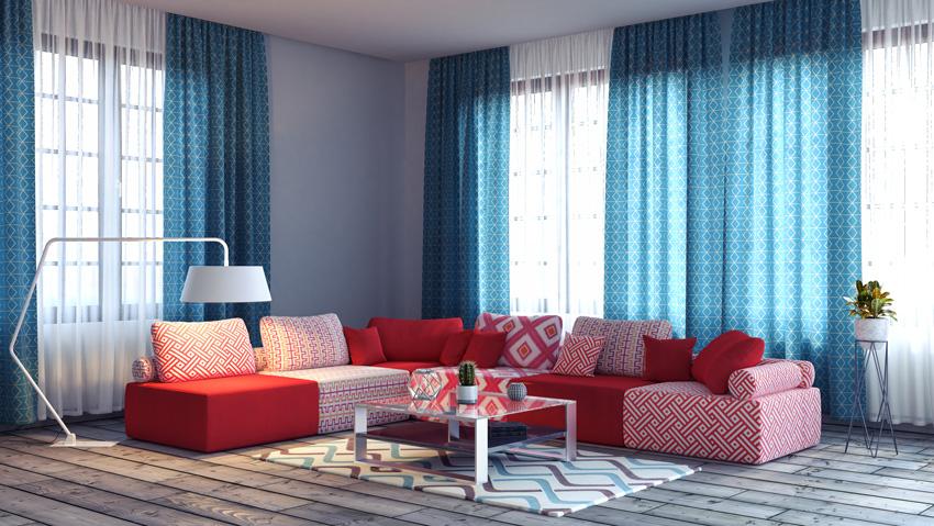 tende a doppio tendaggio blu in un soggiorno moderno con divano ad angolo rosso e bianco.