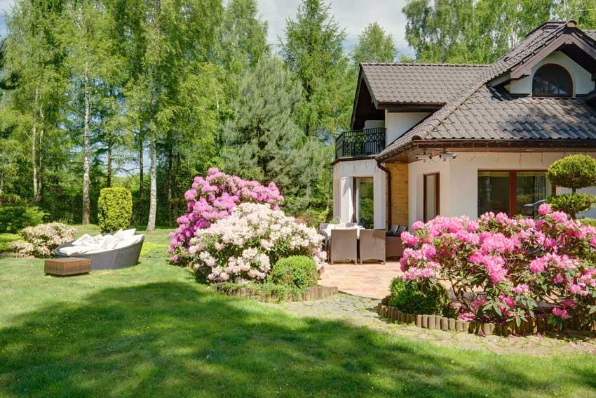 villa con aiuole di fiori realizzati con una bordura in paletti di legno.