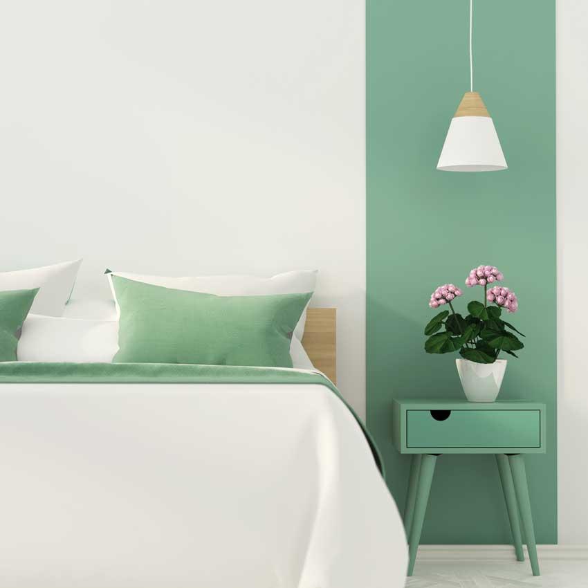 camera da letto con pareti bianche e verde chiaro, bel contrasto con lampadario bianco.