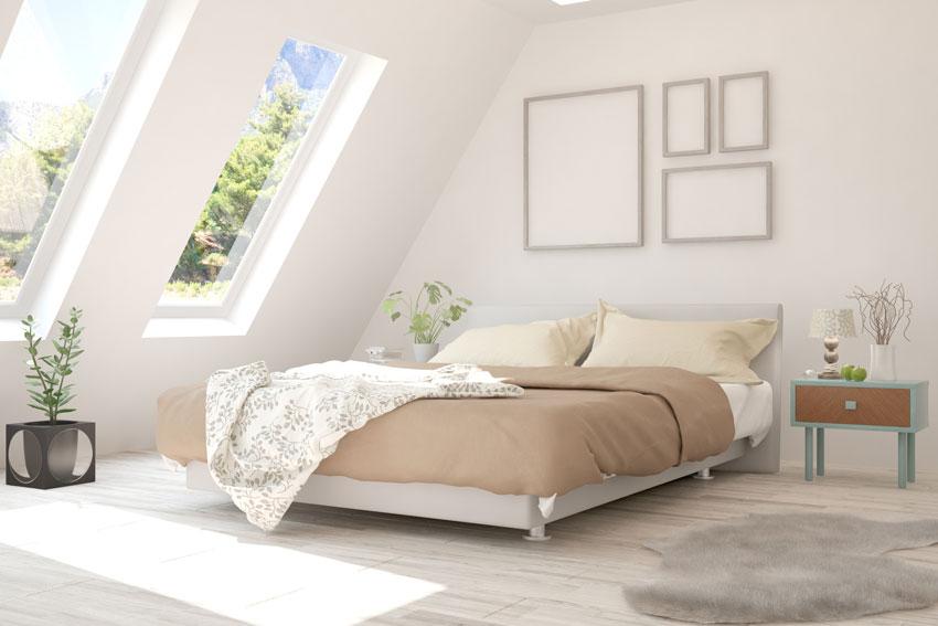 stanza da letto in mansarda, letto matrimoniale con coperte tortora, comodino moderno.