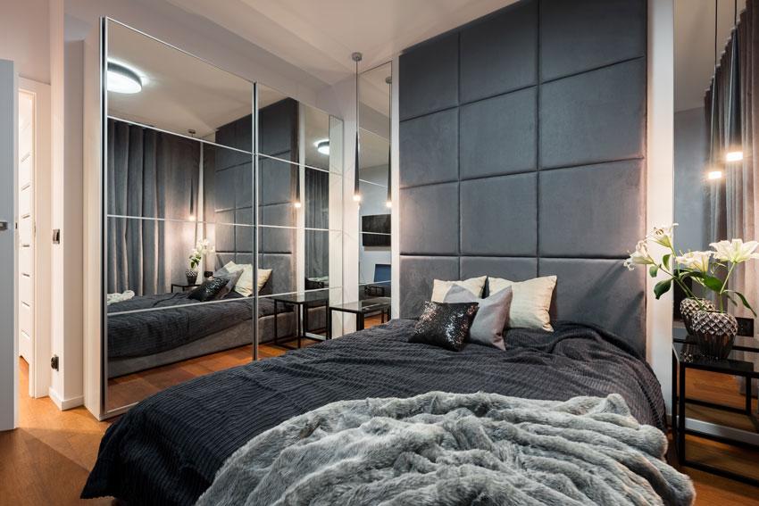 camera da letto moderna con armadio a specchio e letto con alta testiera in pelle nera.