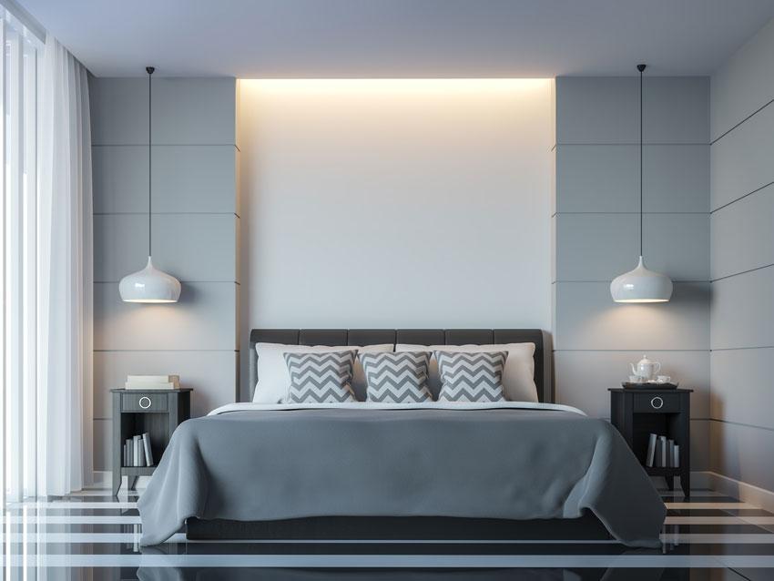 camera moderna grigia e bianca con lampadari a sospensione, pareti in cartongesso con luci a led.