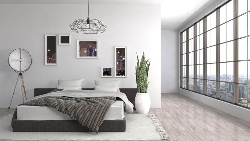 Lampadario e mobili moderni in camera da letto, parete bianca con quadri.