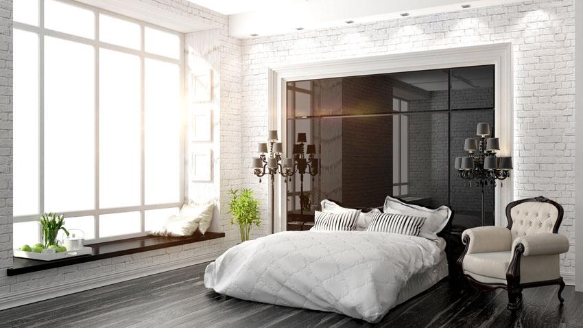 Bella camera da letto moderna con parete in mattoncini bianchi, poltrona da camera stile shabby.