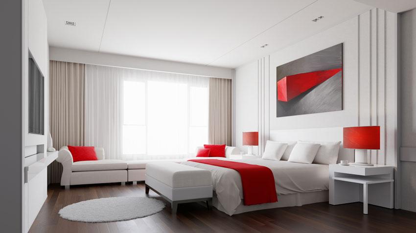 camera da letto bianca con complementi di arredo rossi, stile moderno.