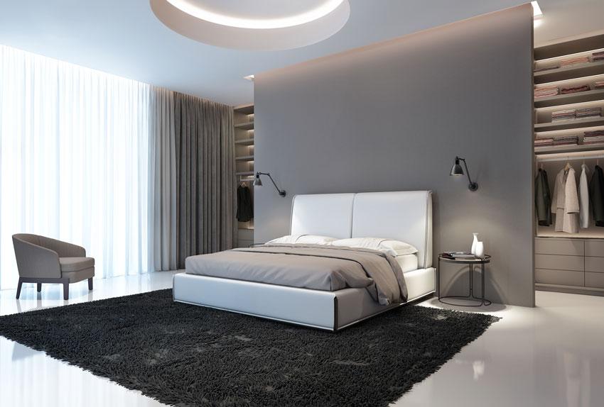 Camera da letto moderna con soffitto in cartongesso, parete letto grigia con cabina armadio dietro.