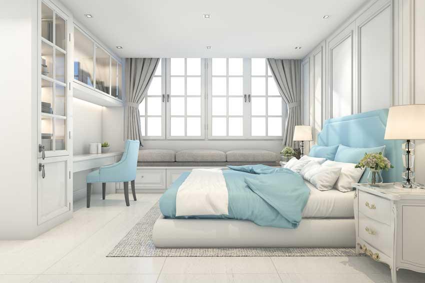 Camera da letto moderne con lenzuoli e sedia colore azzurro, pareti e mobili bianchi.