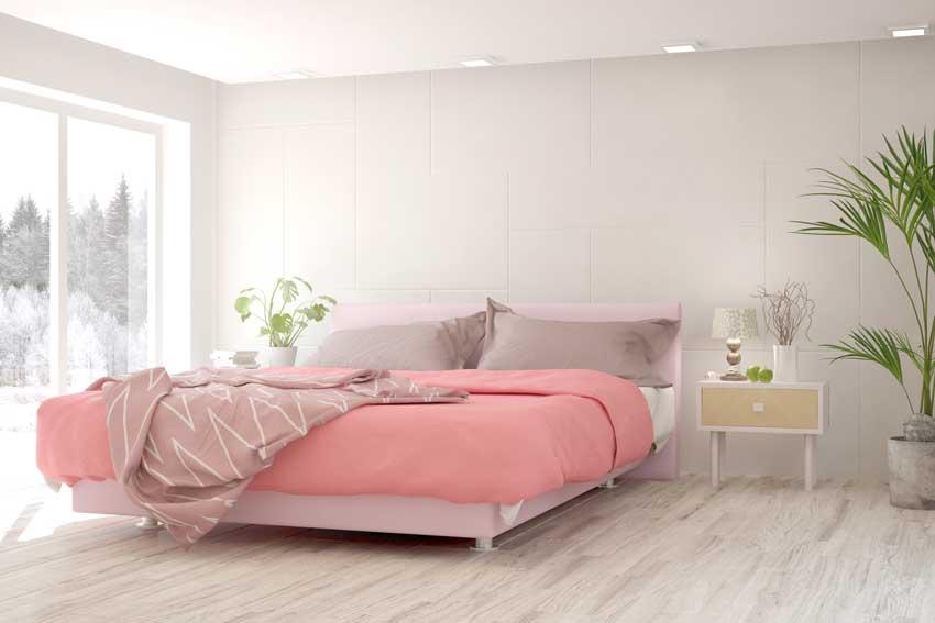 Camera da letto moderna bianca e rosa con piante verde.