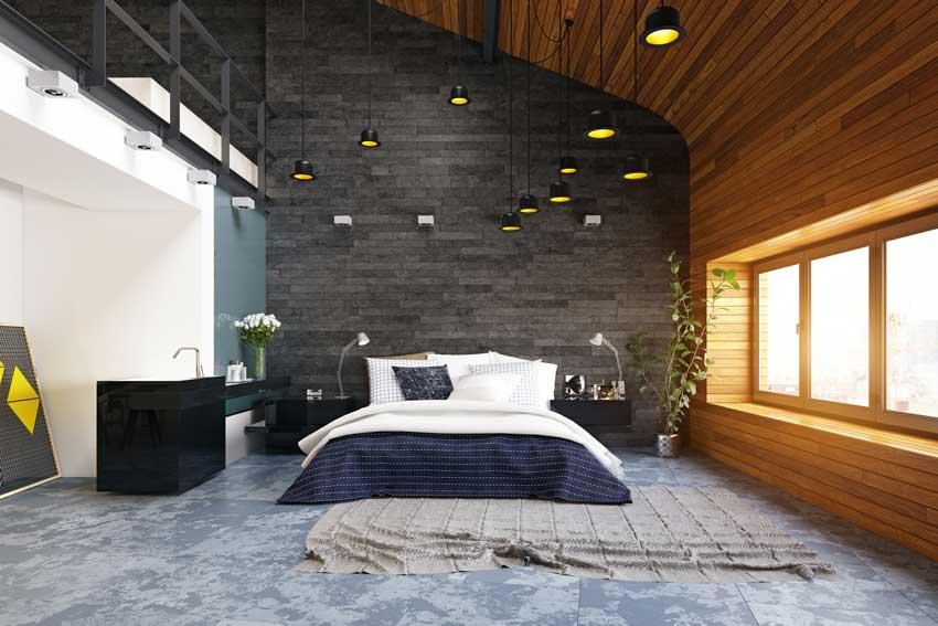 Parete in pietra scura in questa stanza da letto moderna, illuminazione con lampadine sospese.
