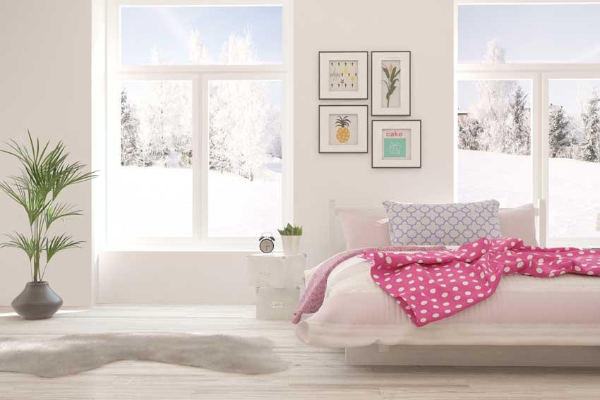 Camera da letto design bianca con piante, lenzuoli rosa e quadri su parete.