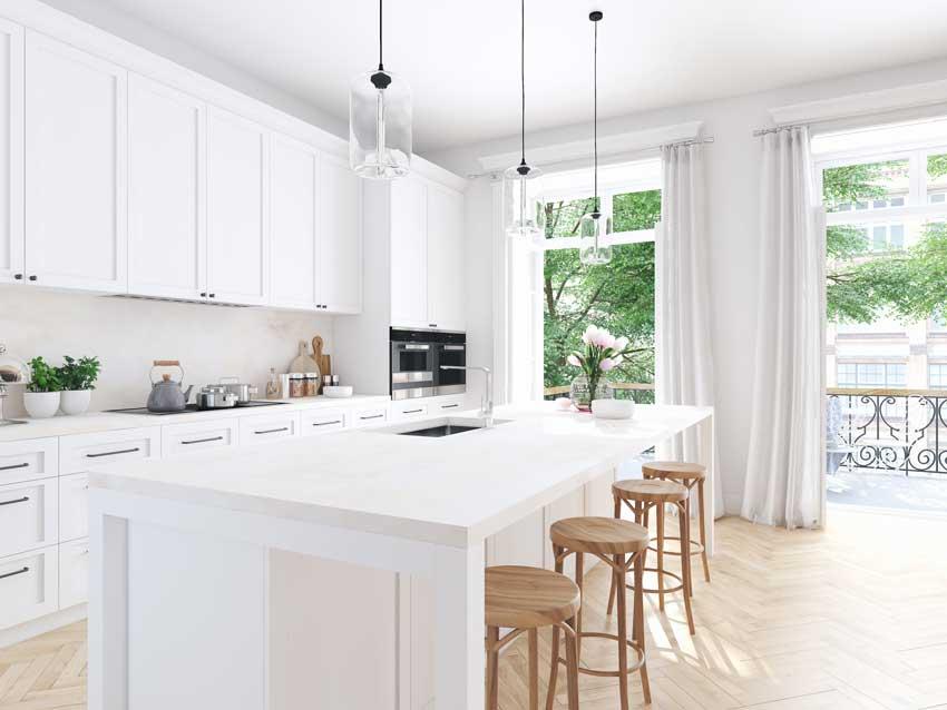Cucina total white con isola moderna e sgabelli in legno chiaro.