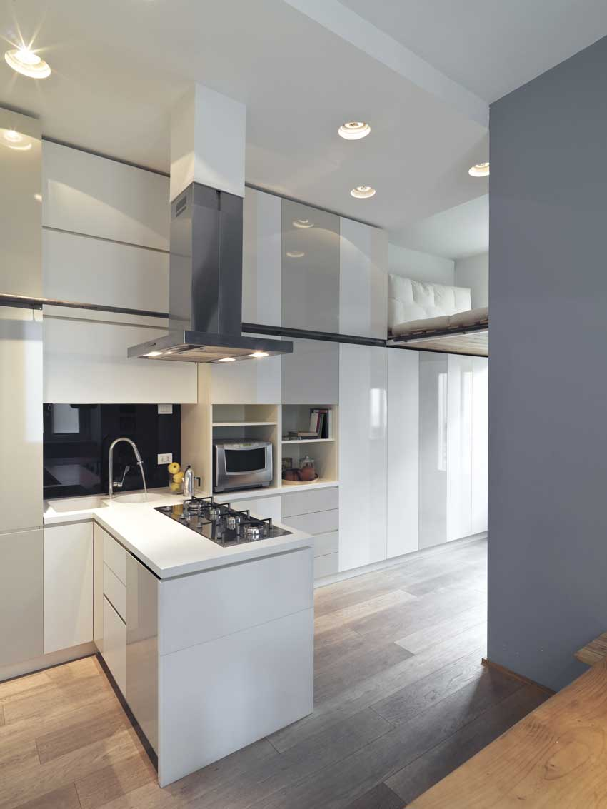 Cucina contemporanea con penisola che ritaglia e da movimento all'ambiente, color bianco e grigio.