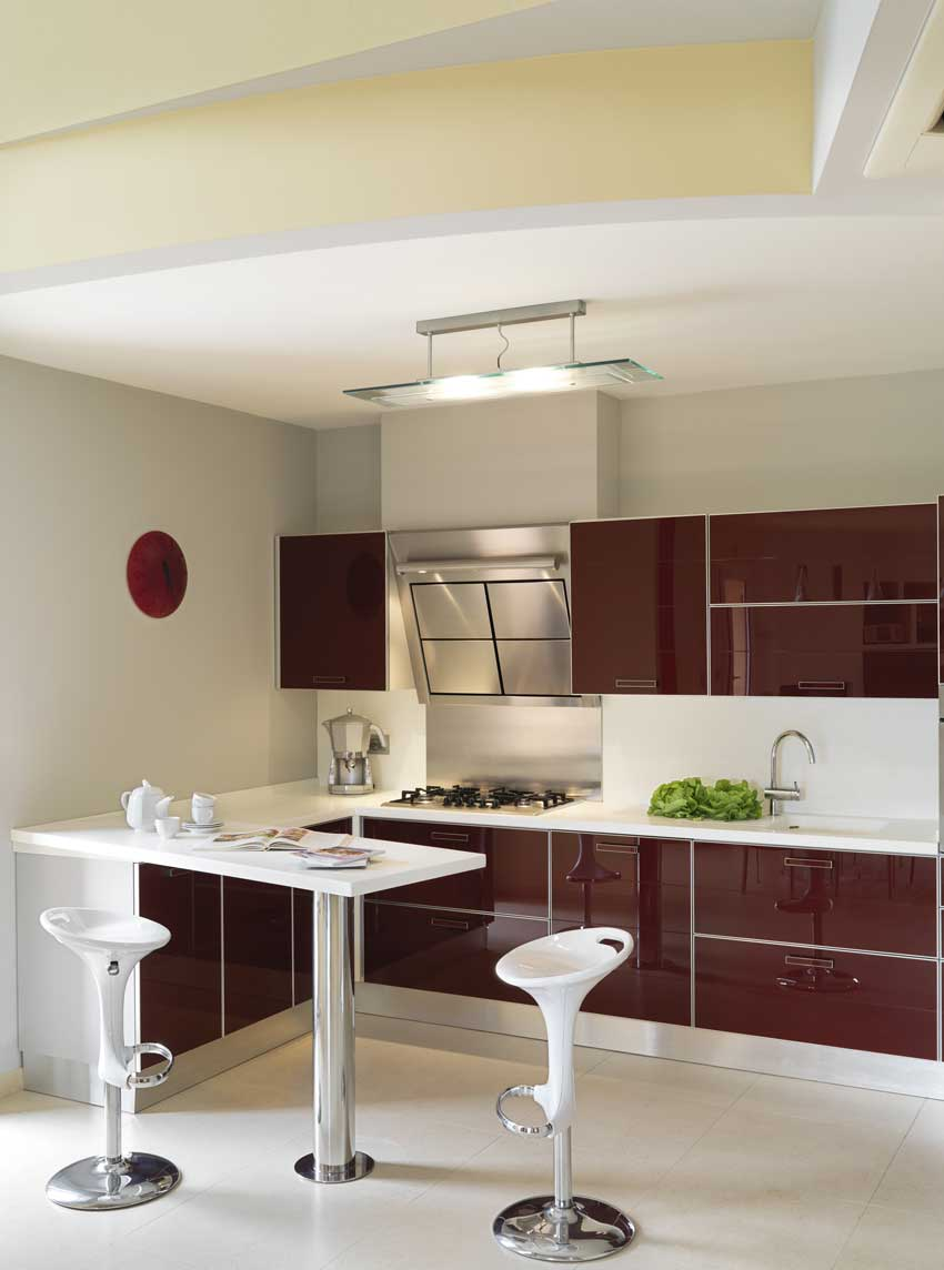 cucina moderna con mobili color bordeaux laccato, piccola penisola bianca con sgabelli.