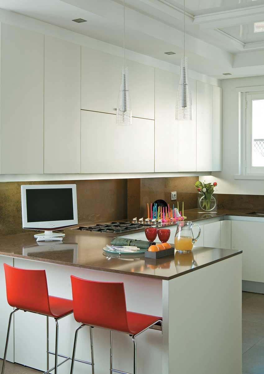 Penisola cucina con televisione e sgabelli rossi, ideale per gustare una buona colazione.