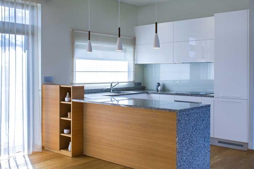 Penisola cucina con rivestimento in legno su lato soggiorno, mobili bianco lucido.