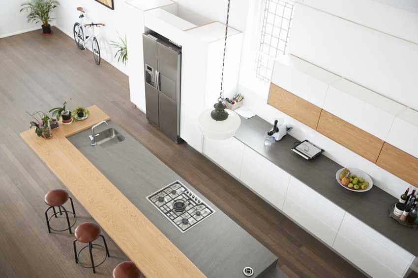 Grande cucina lineare con isola moderna dotata di fornelli e lavabo, enorme piano di lavoro da sfruttare per i pasti e come appoggio per cucinare.