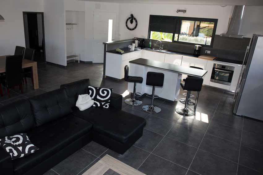 Salotto open space nero e bianco con cucina a vista con isola centrale.