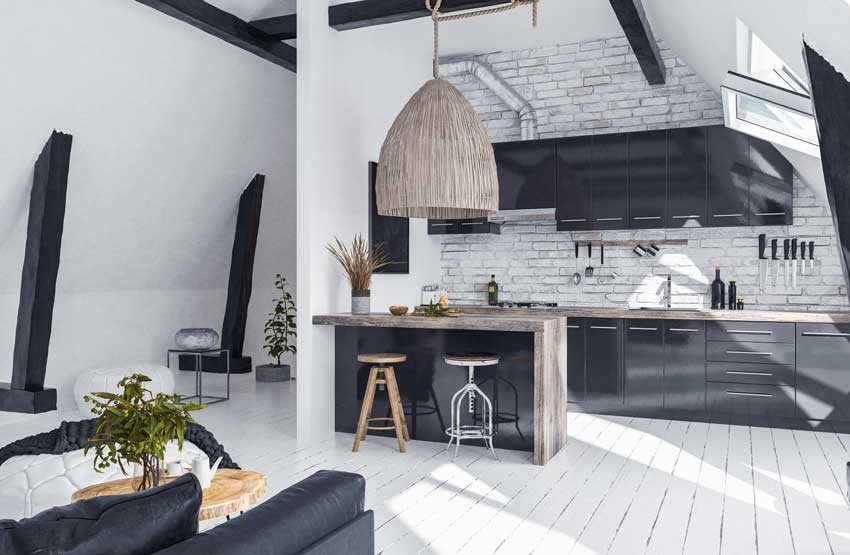 Cucina moderna con penisola e grande lampadario, parete in pietra e piano lavoro in legno grezzo.
