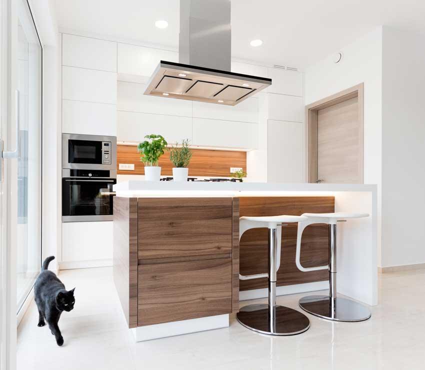 Un esempio perfetto di integrazione di una isola in una piccola cucina bianca e legno.