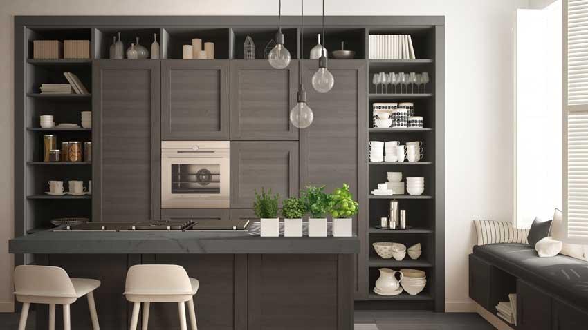 Cucina con isola e parete attrezzata in legno grigio, dal gusto vintage e ideale in un ambiente piccolo.