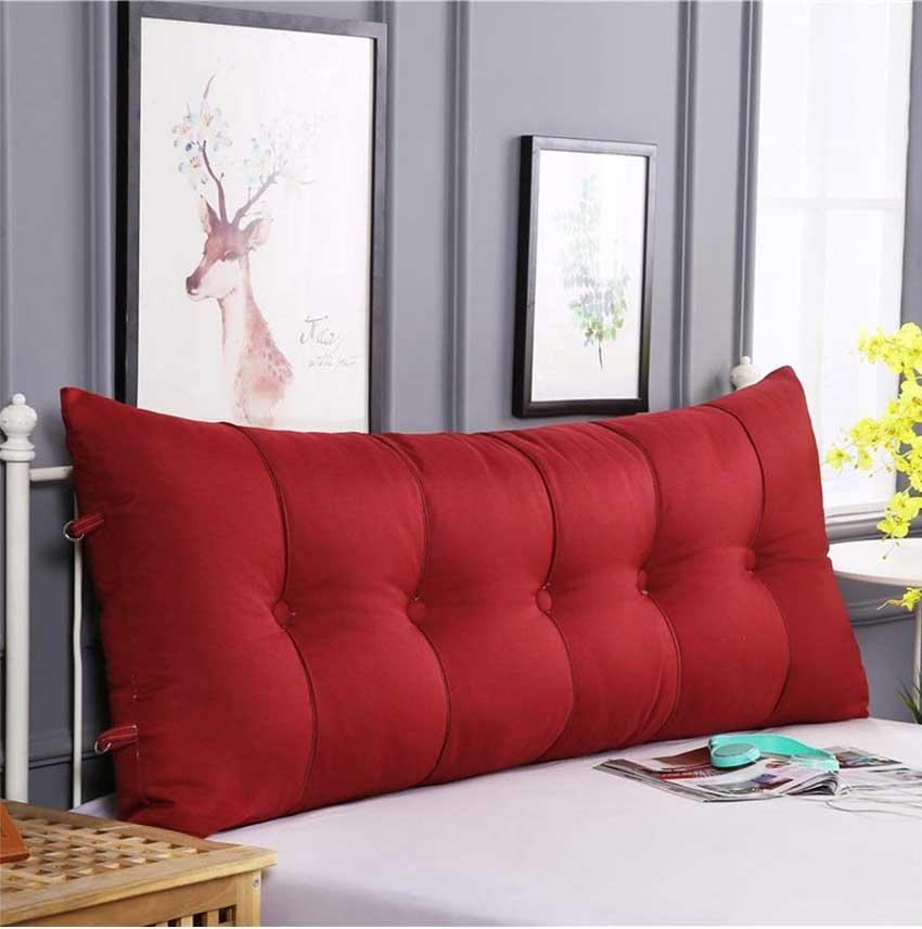 Cuscino rosso per testiera letto, ideale in una camera moderna.