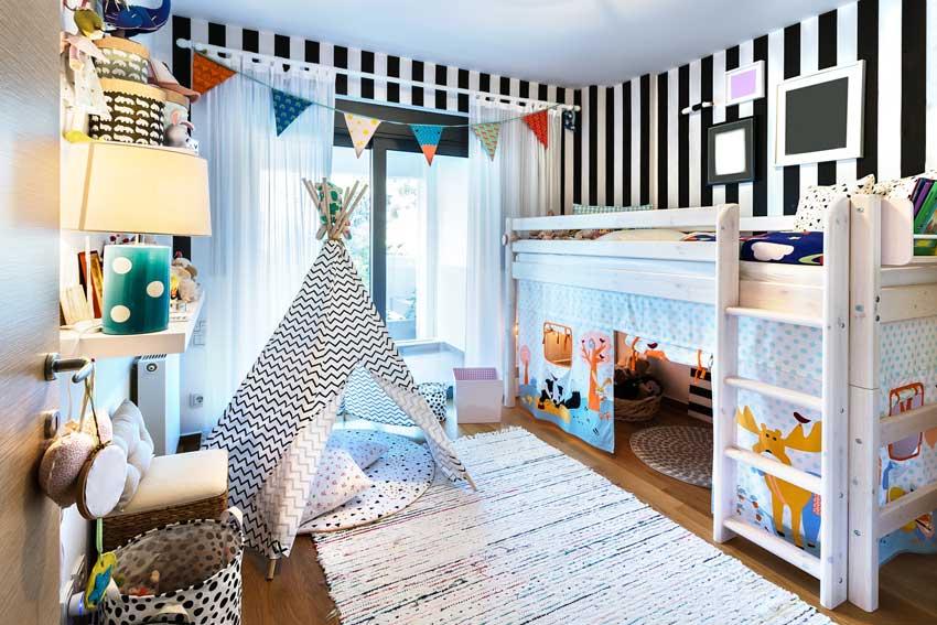 Cameretta per bambini con parete a strisce bianche e nere, letto a soppalco.