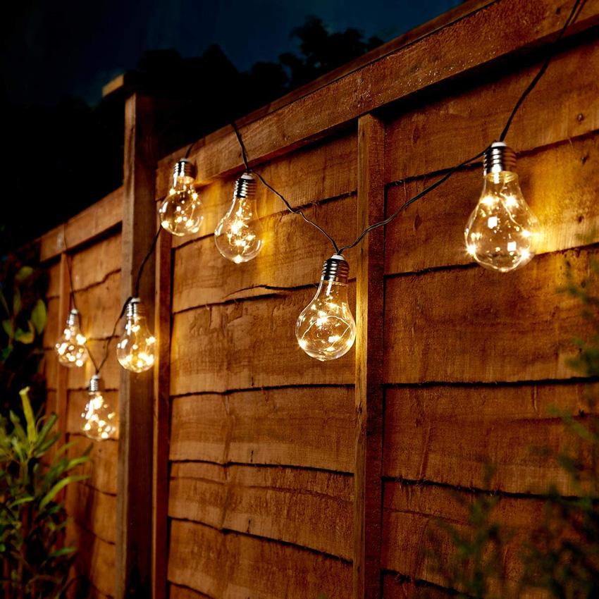catena di lampadine luminose ad energia solare sopra recinto in legno.