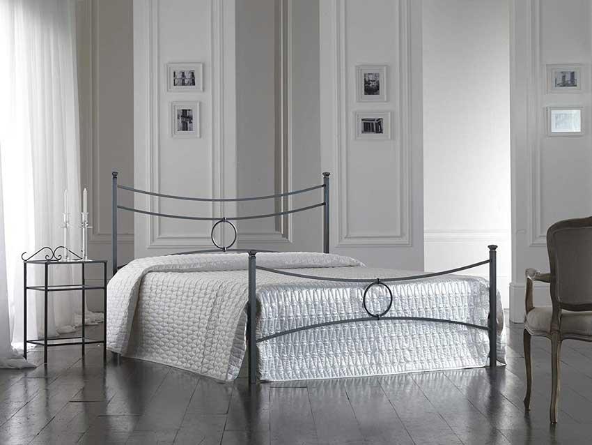 Letto in ferro battuto dal design moderno, pareti con boiserie bianca.