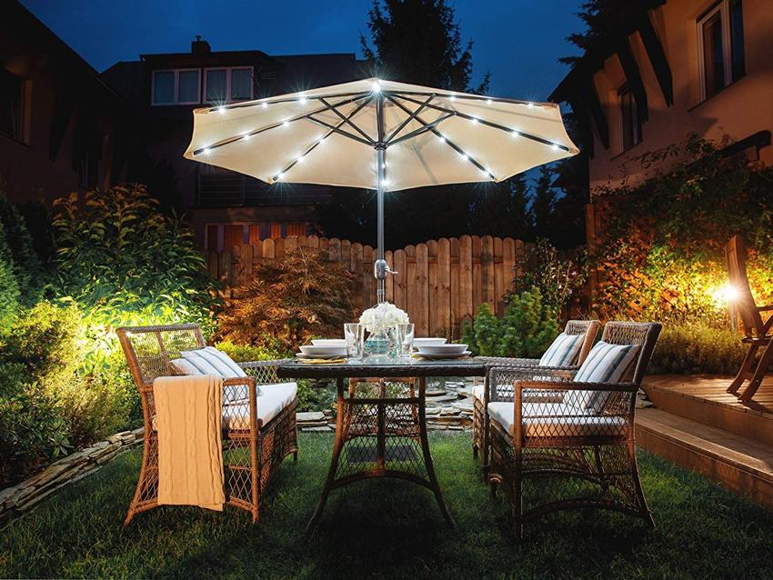 Ombrellone con luci solari LED con tavola da pranzo in giardino.