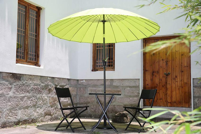 Ombrellone verde design su terrazzo, tavolino con due sedie nere.