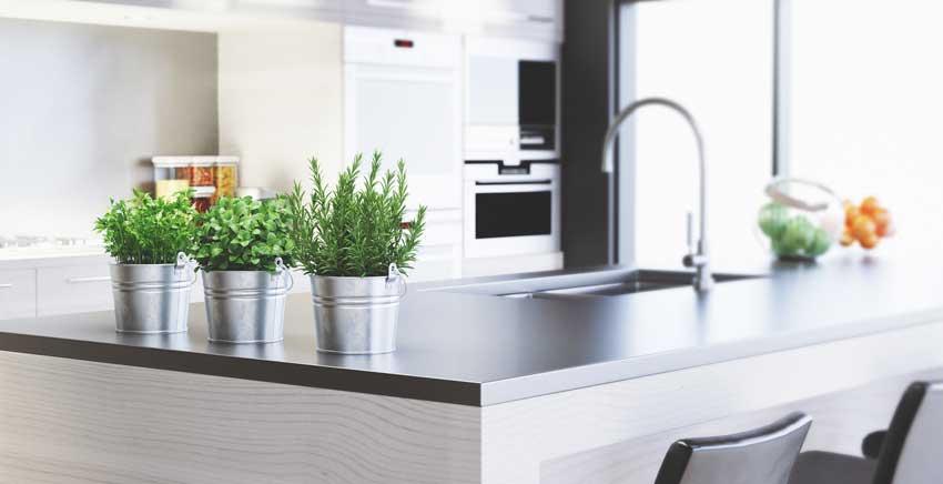 3 vasetti ikea con piantine aromatiche su top cucina.