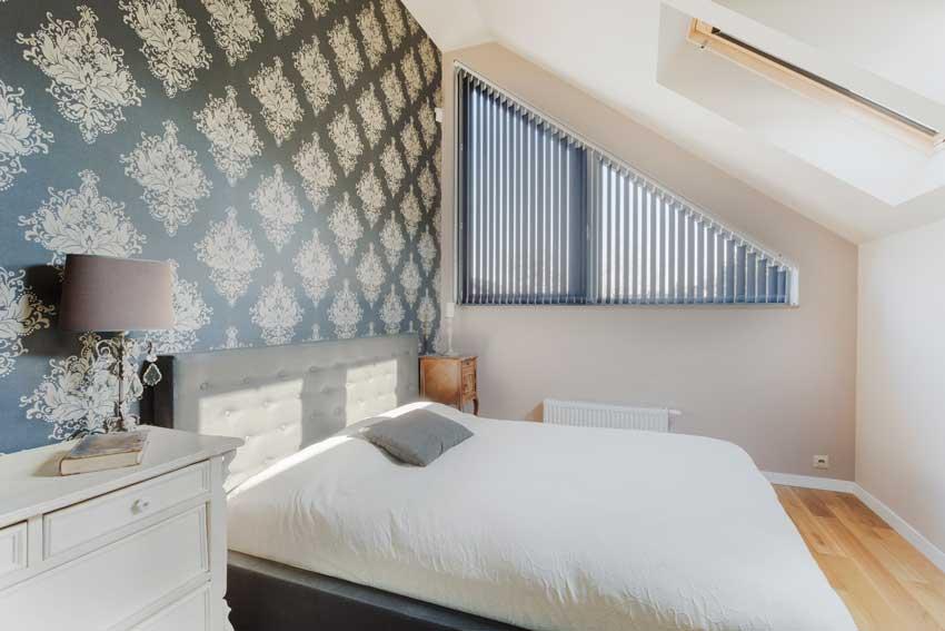 Arredamento in mansarda di un piccola camera da letto moderna.