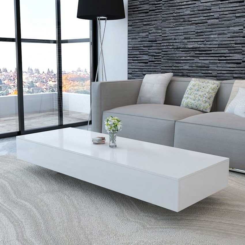 soggiorno moderno con tavolino rettangolare bianco lucido, divano in tessuto grigio e parete effetto pietra.