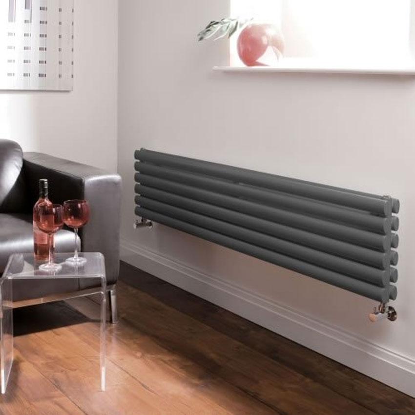 radiatore in acciaio grigio orizzontale in soggiorno vicino al divano.