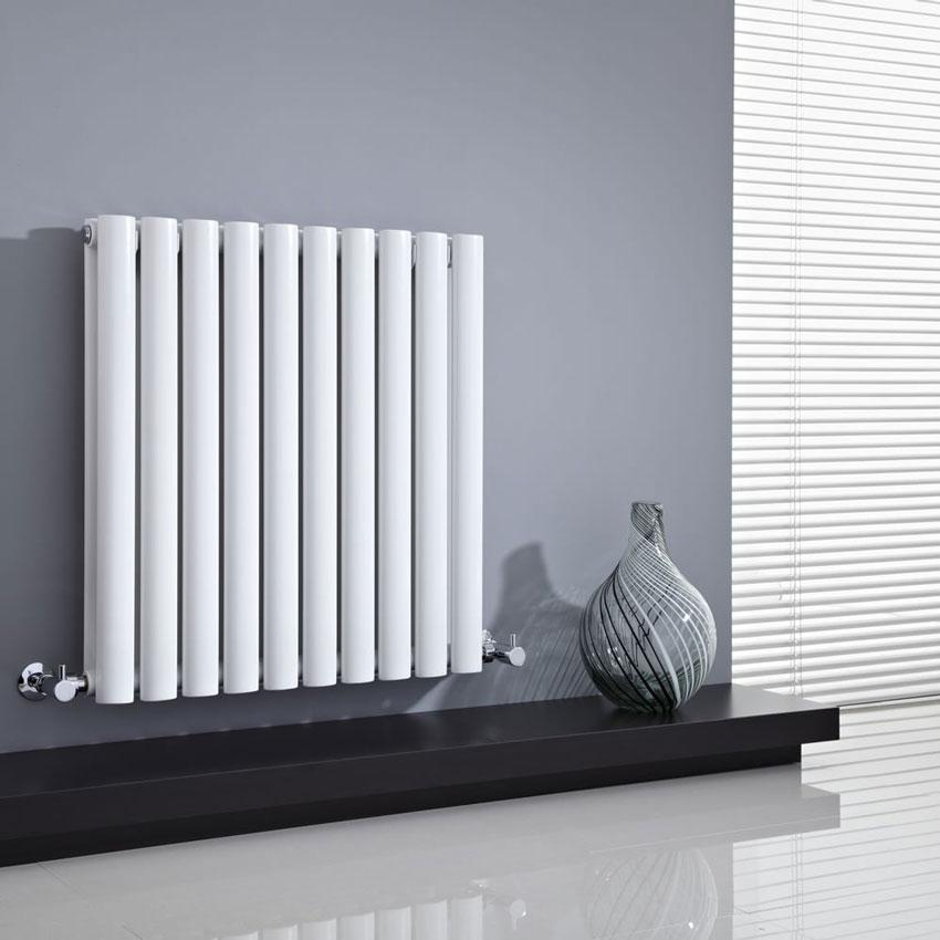 termosifone bianco in acciaio su parete grigia.