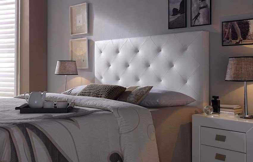 Camera design con testiera letto in pelle bianca imbottita, ideale in un arredamento moderno.