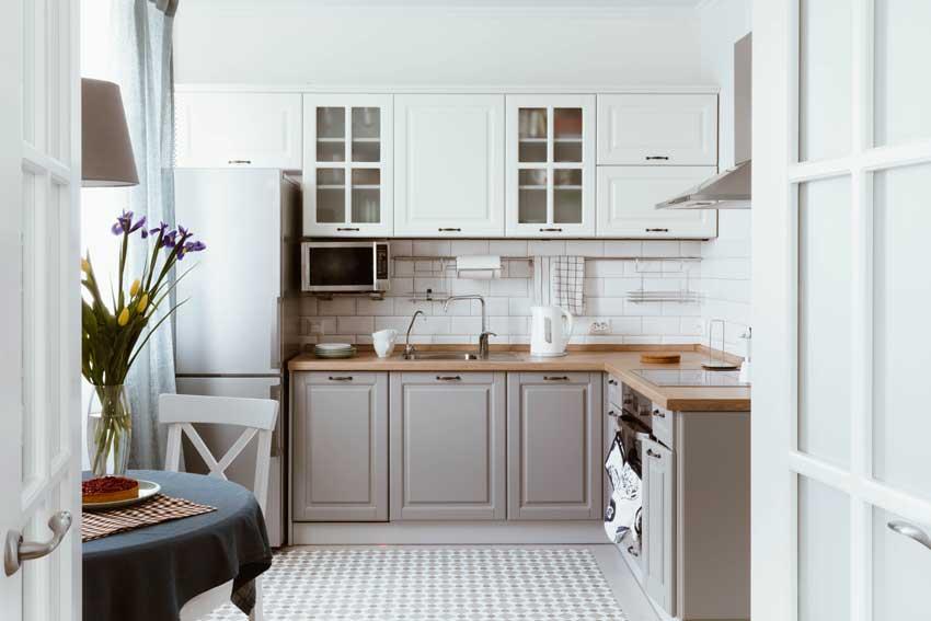 Cucina angolare moderna con pensili bianchi e mobili bassi grigi.