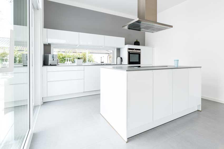 Cucina bianca stile minimalista con isola centrale e cappa sospesa in inox.