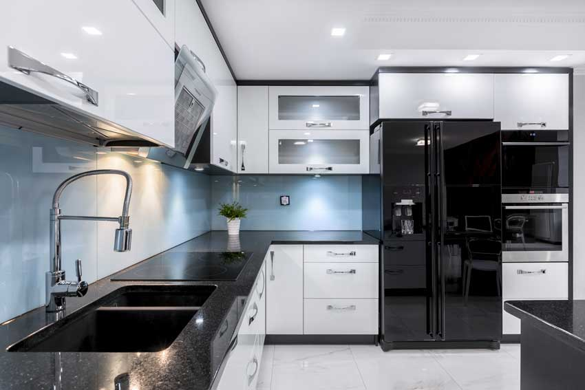 Cucina angolare bianca e nera con rifiniture lucide, ideale per arredare in stile moderno.